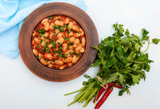White large beans in sweet and sour tomato sauce in a clay bowl on a light background Royalty Free Stock Image