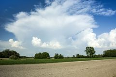 White large cloud in the sky above fields and trees