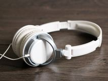 White large headphones on wooden background, music object. White large headphones on wooden background, style music object so close royalty free stock images