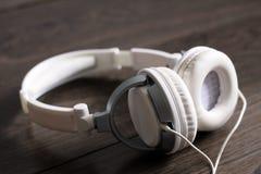 White large headphones on wooden background, music object. White large headphones on wooden background, style music object so close, black and white royalty free stock image