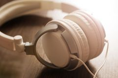 White large headphones on wooden background, music object. White large headphones on wooden background, style music object so close stock images
