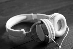 White large headphones on wooden background, music object. White large headphones on wooden background, style music object so close, black and white stock image