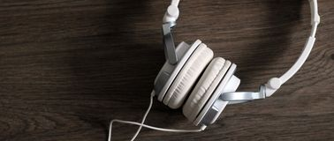 White large headphones on wooden background, music object. White large headphones on wooden background, style music object so close stock photo