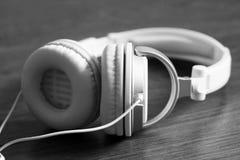White large headphones on wooden background, music object. White large headphones on wooden background, style music object so close, black and white stock photo