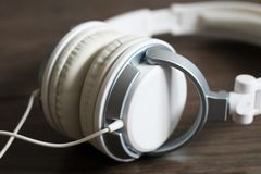 White large headphones on wooden background, music object. White large headphones on wooden background, style music object so close stock image