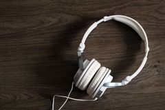White large headphones on wooden background, top view. So close royalty free stock photos