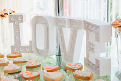 White large lettering love stands before cookies Stock Photos