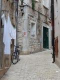 WHITE LAUNDRY, BICYCLE AND A NARROW COBBLESTONE STREET, ROVINJ, CROATIA Royalty Free Stock Photos
