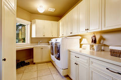 White laundry room interior with tile floor and cabinets. House interior Royalty Free Stock Photo
