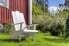 White lawn chair in summer garden Stock Image