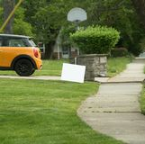 Lawn sign near driveway with yellow car. White lawn sign on lawn of home with car in driveway near sidewalk. Basketball backboard in background. Space for copy royalty free stock photo