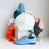 White leather bag (daypack) with clothing, shoes and sunglasses pocked out over the top Stock Photo