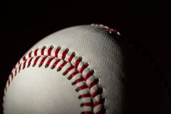 A white leather baseball on a black background