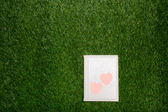 White leather book with hearts lying on the grass Stock Photo