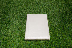 White leather book lying on the grass Royalty Free Stock Photos