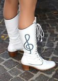 White leather boots with embroidered treble clef above Royalty Free Stock Images