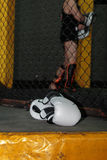 White Leather Boxing Gloves on Floor inside MMA Cage Royalty Free Stock Images