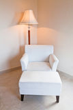 White leather chair and stand lamp Stock Photography
