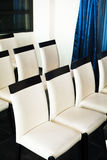 White leather chairs in a hall for conferences and lectures. White leather chairs in a hall for conferences and workshops Royalty Free Stock Photos