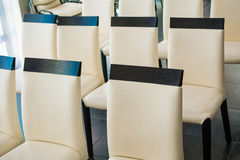 White leather chairs in a hall for conferences and lectures. White leather chairs in a hall for conferences and workshops Royalty Free Stock Photography