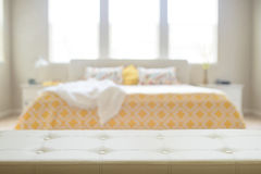 White leather empty bench in front of blurred bedroom. In yellow and beige colors. Display of products royalty free stock images