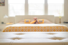 White leather empty bench in front of blurred bedroom. In yellow and beige colors. Display of products royalty free stock photography