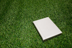 White leather empty book lying on the grass Royalty Free Stock Photography
