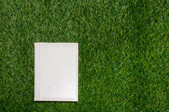White leather empty book lying on the grass Stock Images