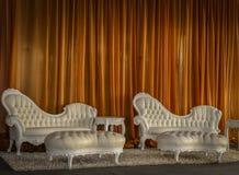 White leather furniture setting. Gold drape background to white leather furniture setting Stock Image