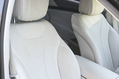 White leather interior of the luxury modern car. Leather comfortable white seats and multimedia. exclusive wood and metal Royalty Free Stock Image