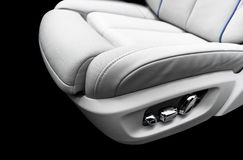 White leather interior of the luxury modern car. Perforated white leather comfortable seats with stitching isolated on blackWhite. White leather interior of the royalty free stock photo