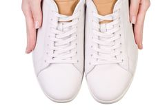 White leather male sneakers shoes on laces in hand. On white background isolation, top view Stock Photos