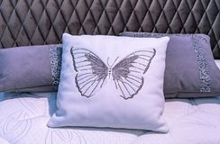White leather pillow with embroidered butterfly in the bedroom interior stock images