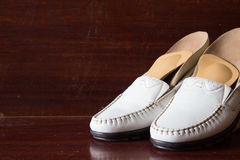 White leather slipper or shoes with orthopedic insoles. Wooden b. Ackground stock photography