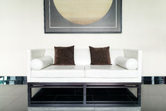 White leather sofa and brown pillow in lounge at living room Stock Images