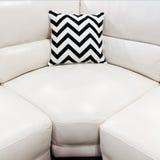 White leather sofa with decorative cushion. White leather sofa with striped decorative cushion. Modern furniture royalty free stock image