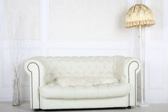 White leather sofa in room with floor lamp Stock Images