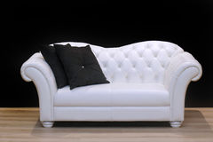 White leather sofa. On wooden floor inside black wall interior Stock Image