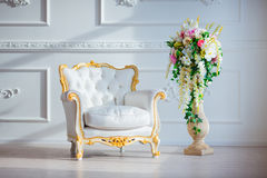 White leather vintage style chair in classical interior room with big window and spring flowers Stock Photography