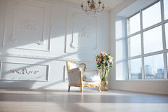 White leather vintage style chair in classical interior room with big window and spring flowers Stock Photo