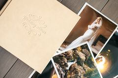 White leather wedding album and printed photos with the bride and groom stock photo