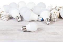 White LED bulb lights and fluorescent tube lamps. On gray wooden board and white background stock photography