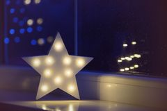 White LED star near window on garland bokeh background indoor in evening time. Festive spring illumination, holiday atmosphere royalty free stock photography