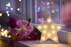 White LED star with pink tulips on warm bokeh background indoor stock images
