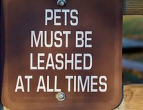 Pets must be leased at all times sign. White lettering on brown shows pets must be leased at all times Royalty Free Stock Photo