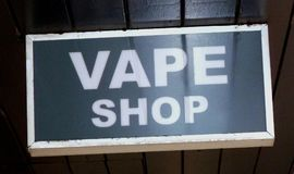 Vape Shop sign electronic cigarettes. White lettering on glass with a white wooden frame hanging from a black painted ceiling stock images