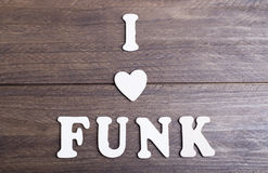 White letters laying on dark wood messaging I love funk. Horizontal studio shot royalty free stock images