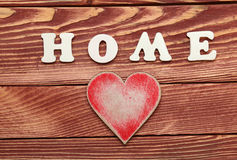 White letters with word HOME and  heart on wooden background Royalty Free Stock Photos