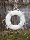 Life Preserver hanging on post at lake bank. royalty free stock photos
