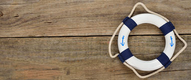 White lifebuoy. On a wooden background Stock Photos